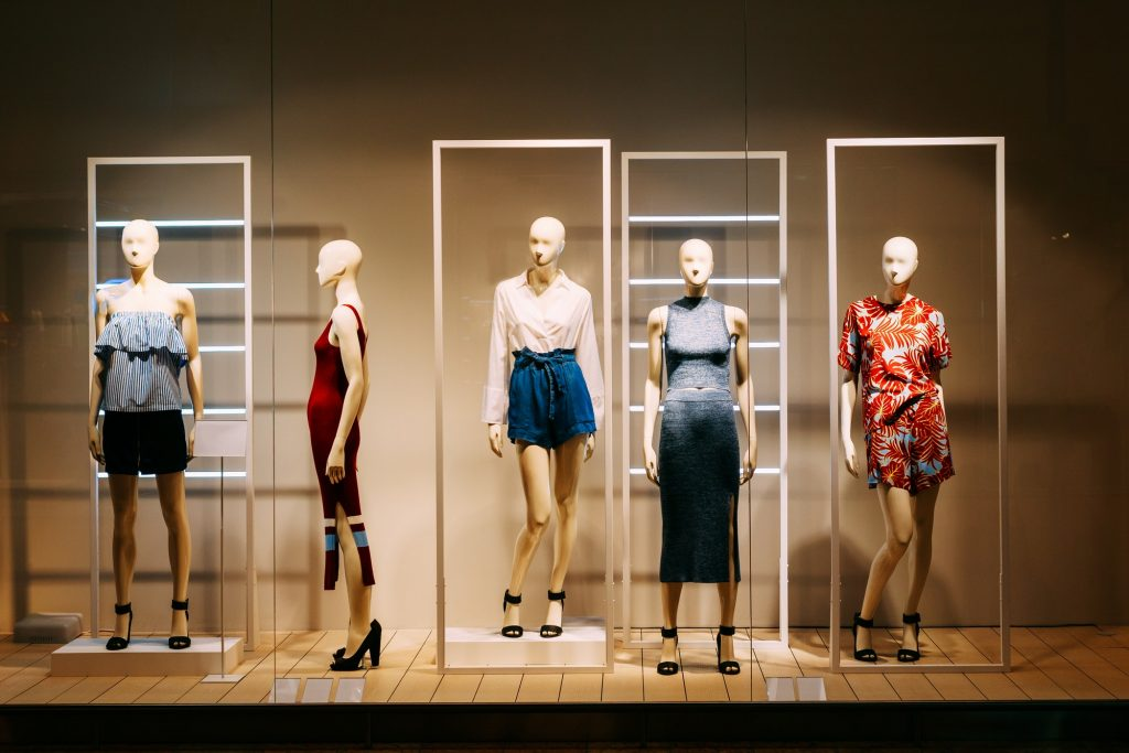 Five Mannequins Standing In Store Window Display Of Women's Casu